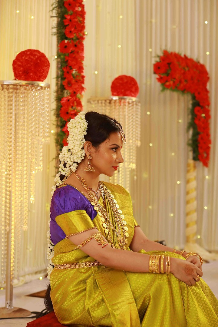 b9e0f4ef6d7b The bride donned a beautiful train of gajra flowers that decorated swept  back braids and a traditional silky green saree with a blue blouse.